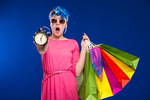 Ragazza con borse e una sveglia in mano Foto Premium