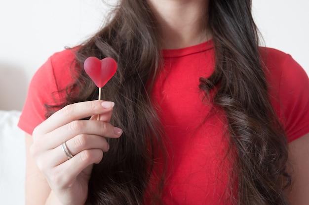 Ragazza con caramelle a forma di cuore nel giorno di san valentino Foto Premium