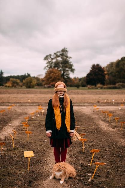 Ragazza con gli occhi bendata dai capelli lunghi che sta nel campo di autunno con il gatto che si siede vicino alle sue gambe. Foto Premium