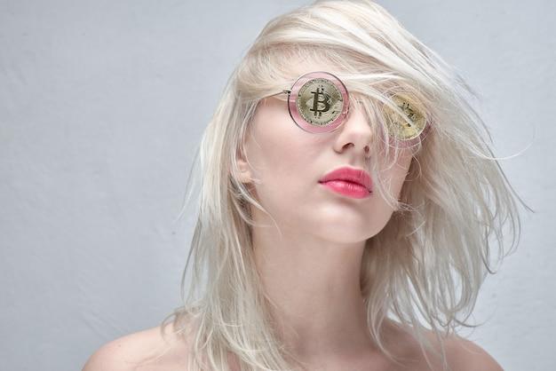 Ragazza con gli occhiali con bitcoin su sfondo bianco Foto Premium