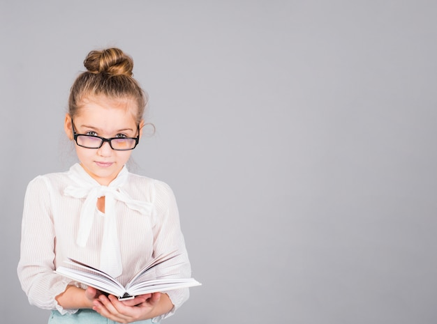 Ragazza con gli occhiali in piedi con il libro Foto Gratuite