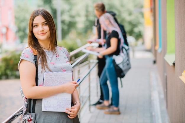 Ragazza con gli studi sul portico universitario Foto Gratuite
