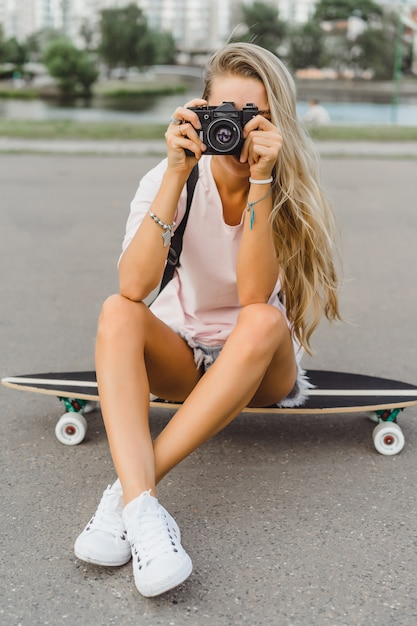 Ragazza con i capelli lunghi con skateboard fotografando sulla fotocamera. strada, sport attivi Foto Gratuite