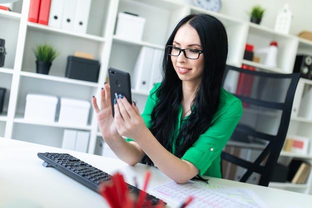 Ragazza con i vetri nell'ufficio che esamina il telefono e sorridere. Foto Premium