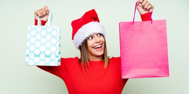 Ragazza con il cappello di natale e con il sacchetto della spesa sopra verde isolato Foto Premium
