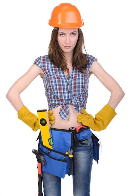 Ragazza con il casco e la cinghia degli strumenti su bianco. Foto Premium