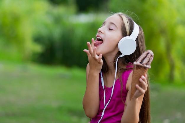 Ragazza con il gelato che lecca le dita Foto Gratuite