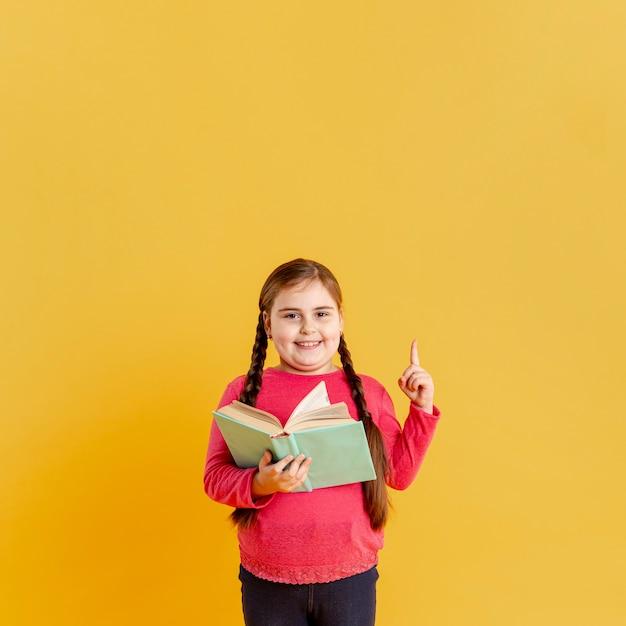 Ragazza con il libro che punta sopra Foto Gratuite