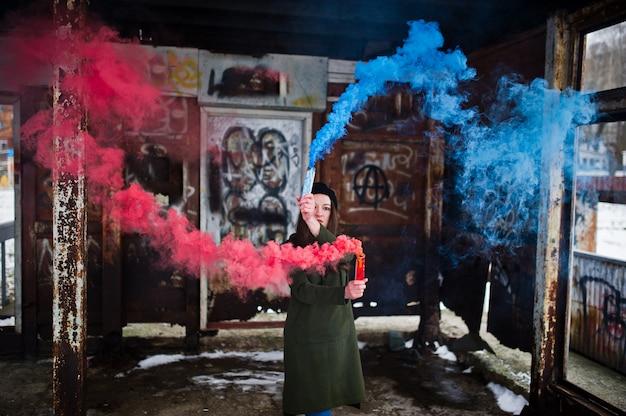 Ragazza con la bomba fumogena colorata blu e rossa in mani. Foto Premium