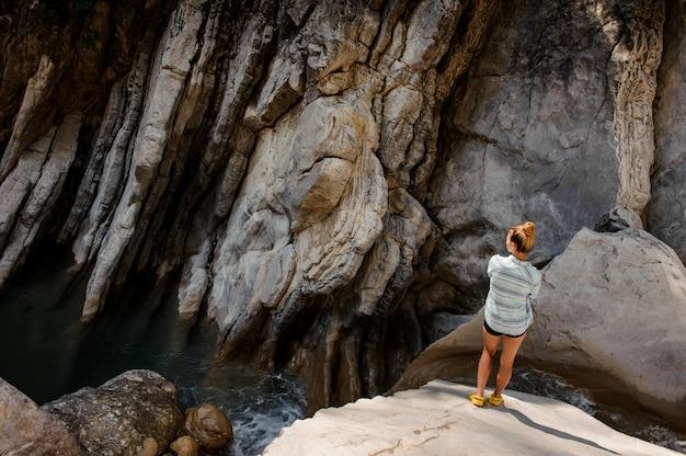 Ragazza con la coda di cavallo che sta cascata vicina in canyon Foto Premium