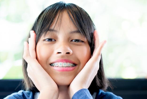 Ragazza con le parentesi graffe dentali che sorride e felice Foto Premium