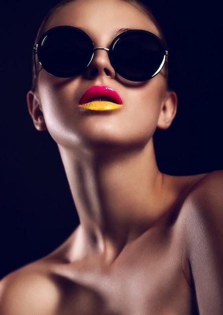 Ragazza con occhiali da sole e due tonalità di labbra in posa Foto Gratuite