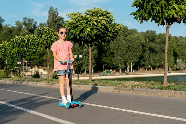 Ragazza con occhiali da sole in sella a scooter Foto Gratuite
