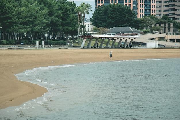 Ragazza con ombrello in attesa e stare sulla spiaggia Foto Premium