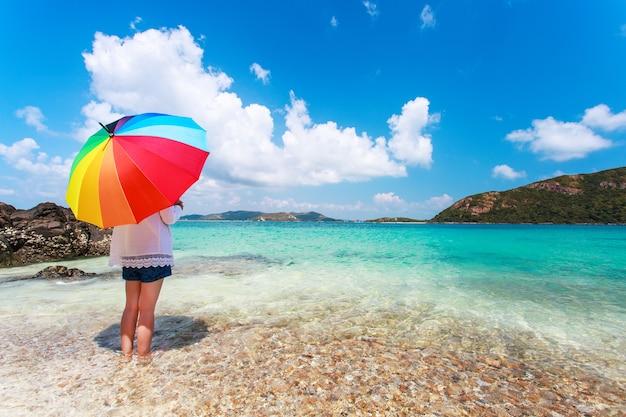 Ragazza con ombrello pieno di colore sulla spiaggia sabbiosa Foto Premium
