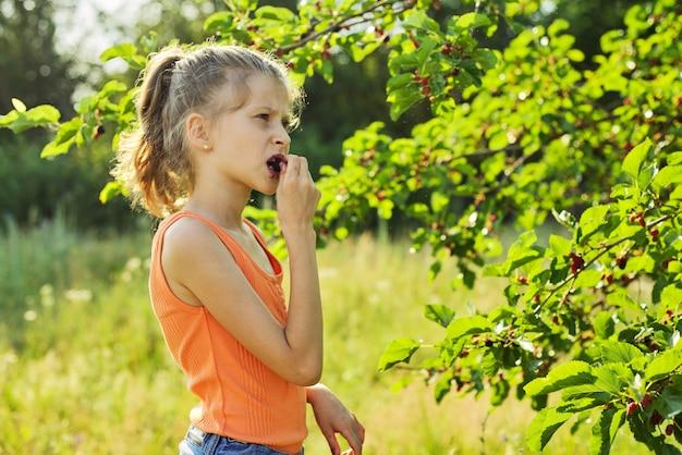 Ragazza con piacere che mangia le bacche mature dolci deliziose dall'albero di gelso Foto Premium