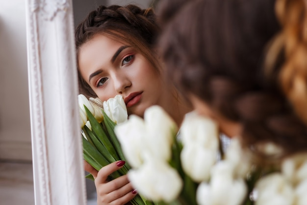 Ragazza con tulipani bianchi in studio riflesso nel ritratto specchio. look estivo. trucco e acconciatura. bruna. foto tenera Foto Premium