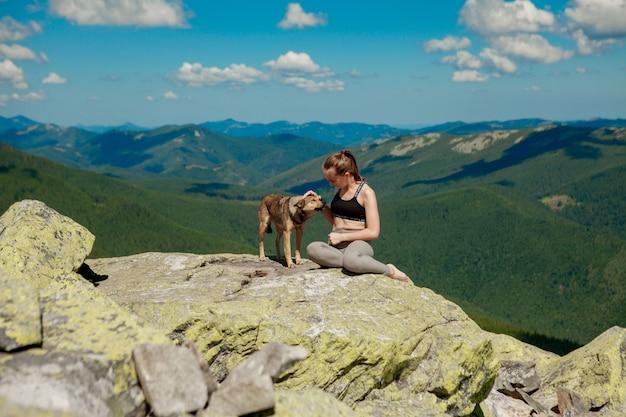 Ragazza con un cane in cima a una montagna a guardare un bellissimo paesaggio con le braccia spalancate Foto Premium