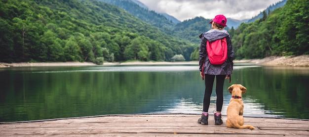 Ragazza con un cane in piedi sul molo sul lago Foto Premium