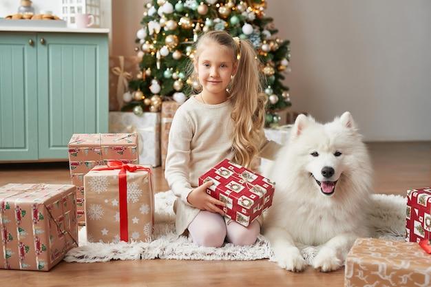 Ragazza con un cane vicino all'albero di natale sulla scena di natale Foto Premium