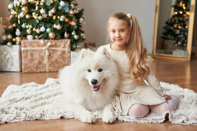 Ragazza con un cane vicino all'albero di natale sullo sfondo di natale Foto Premium