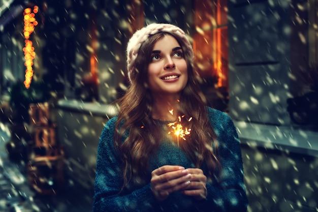 Ragazza con un'insegna di inverno delle luci di bengala Foto Premium
