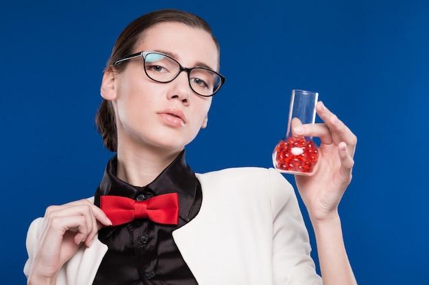 Ragazza con una fiala in mano e una farfalla rossa sul collo Foto Premium