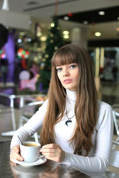 Ragazza con una tazza di caffè in un centro commerciale sullo sfondo dell'albero di natale Foto Premium