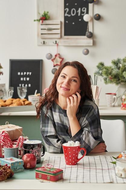 Ragazza con una tazza nella cucina di capodanno Foto Premium