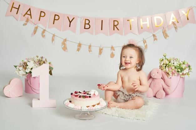 Ragazza con una torta di compleanno, sessione fotografica di un bambino di 1 anno Foto Premium