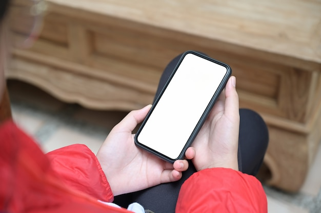 Ragazza con uno smartphone mobile schermo vuoto nelle sue mani Foto Premium