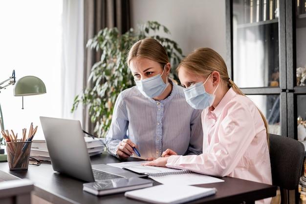 Ragazza d'aiuto della donna con i compiti mentre indossa una maschera medica Foto Gratuite