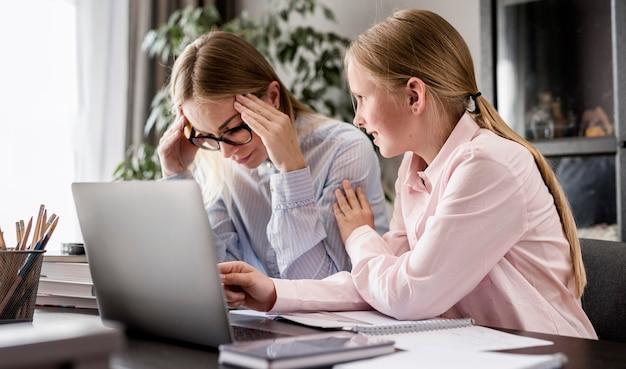 Ragazza d'aiuto della donna di vista laterale con i compiti Foto Gratuite