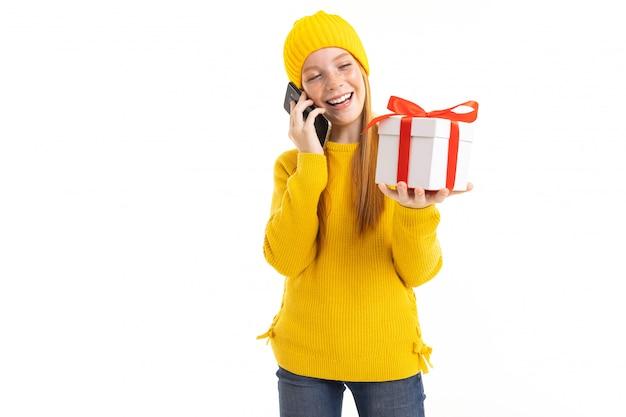 Ragazza dai capelli rossi europea che parla sul telefono con un regalo in sue mani su un bianco Foto Premium
