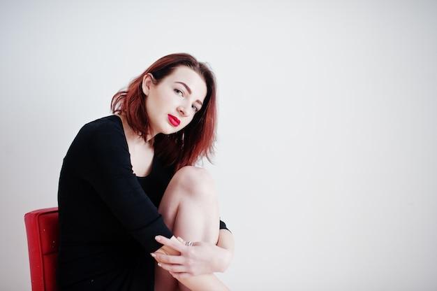 Ragazza dai capelli rossi sulla tunica nera vestito seduto sulla sedia rossa contro il muro bianco a stanza vuota. Foto Premium