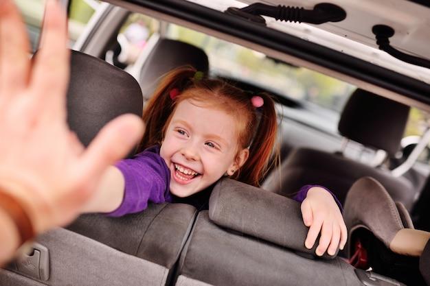 Ragazza dai capelli rossi sveglia che sorride nel salone dell'automobile Foto Premium
