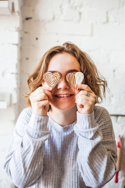 Ragazza dall'aspetto europeo che tiene i biscotti a forma di cuore, amanti, san valentino, cottura, cottura Foto Premium