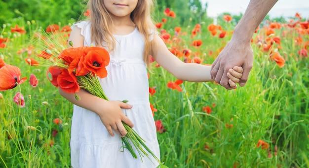Ragazza dei bambini in un campo con i papaveri. Foto Premium