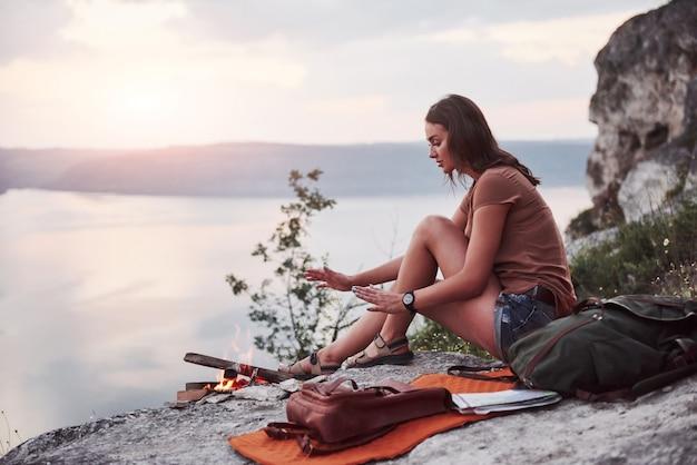 Ragazza dei pantaloni a vita bassa con lo zaino che gode del tramonto sul picco della montagna della roccia. Foto Gratuite