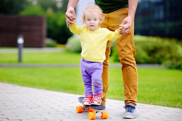 Ragazza del bambino che impara pattinare con suo padre Foto Premium
