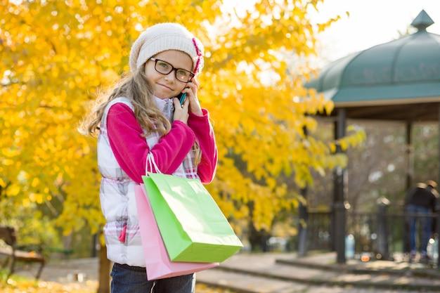 Ragazza del bambino con i sacchetti della spesa e il telefono cellulare Foto Premium