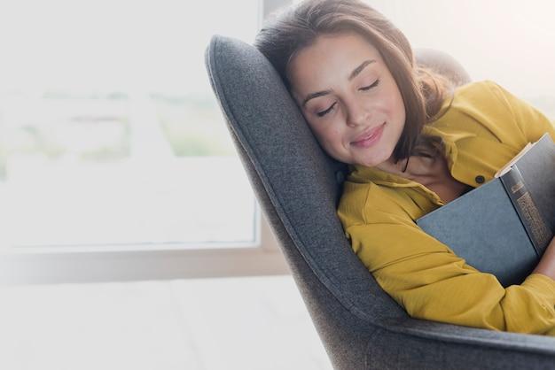 Ragazza del colpo medio che dorme con il libro Foto Gratuite