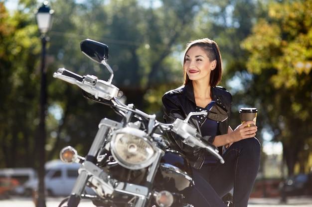 Ragazza del motociclista in una giacca di pelle su una moto Foto Gratuite