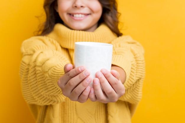 Ragazza del primo piano che tiene tazza con tè caldo Foto Gratuite