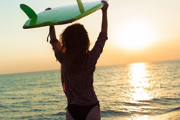 Ragazza del surfista che pratica il surfing guardando il tramonto della spiaggia dell'oceano Foto Premium