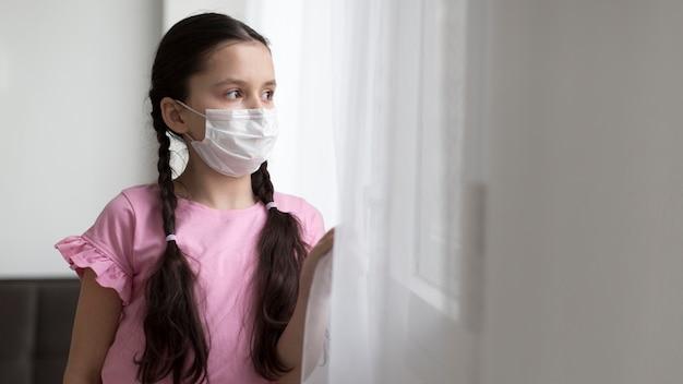 Ragazza del tiro medio che indossa maschera medica Foto Gratuite