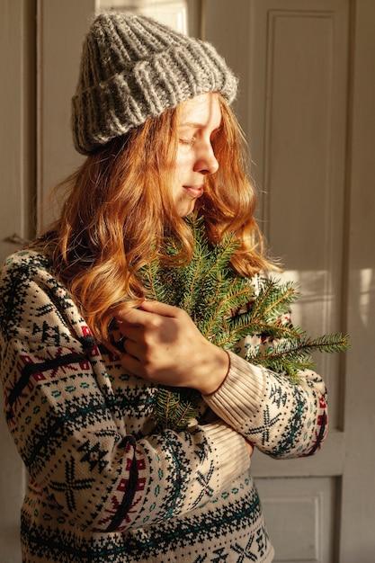 Ragazza del tiro medio con il cappello che tiene i ramoscelli dell'albero di abete Foto Gratuite