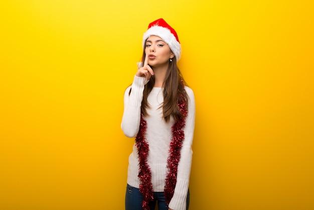 Ragazza dell'adolescente che celebra le feste di natale che mostrano un segno della bocca di chiusura e del gesto di silenzio Foto Premium