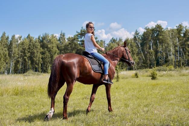 Ragazza dell'adolescente che monta un cavallo marrone, equitazione per le persone nel parco Foto Premium