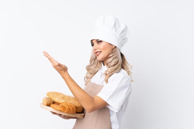 Ragazza dell'adolescente in uniforme del cuoco unico. panettiere femminile che tiene una tavola con parecchi pani sopra le mani estendenti bianche isolate al lato per l'invito a venire Foto Premium